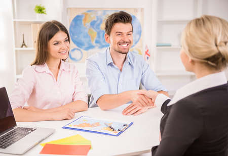 travel agent: Female travel agent greeting happy young couple at office.