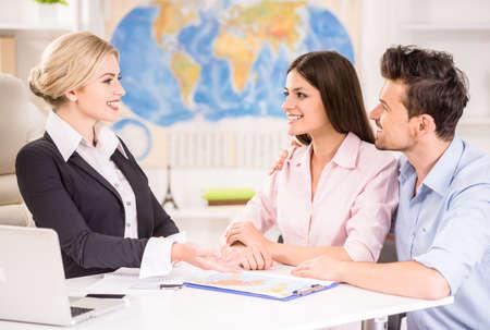 agencia de viajes: Hermosa mujer sentada en la oficina con los clientes y proponer rutas calientes para ellos.