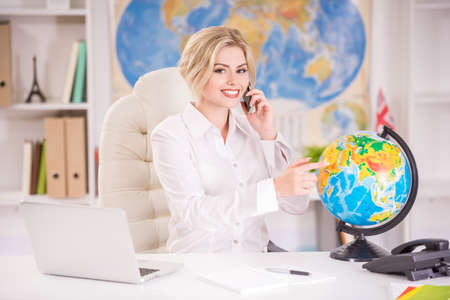 Beautiful travel agent sitting at the table in office and pointing place on globus. Reklamní fotografie