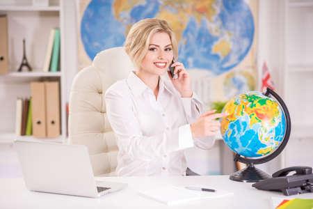 Mooie reisbureauzitting bij de lijst in bureau en het richten van plaats op globus. Stockfoto - 42815894