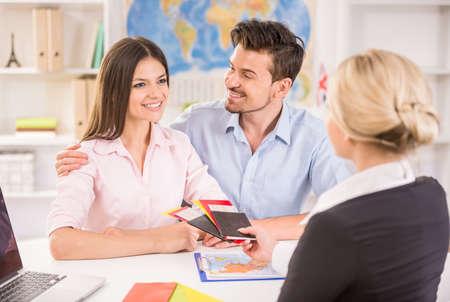 agencia de viajes: Agente de viajes sexo femenino que da entradas para la joven pareja feliz.