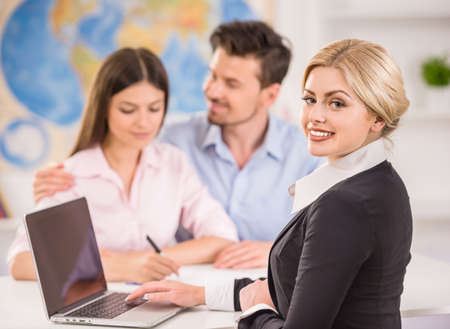 Beautiful woman sitting at office with clients and proposing hot tours to them. Stock Photo