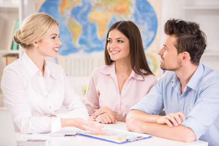 student travel: Beautiful woman sitting at office with clients and proposing hot tours to them.