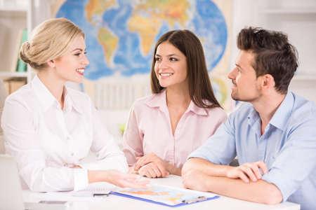 Mooie vrouw zitten op kantoor met klanten en het voorstellen van hete reizen naar hen.