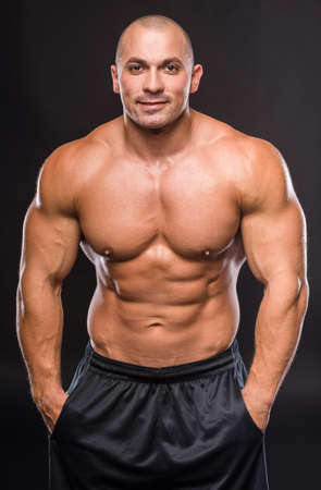 Portrait of a sexy muscular young man posing over dark background. Stock Photo - 42815987