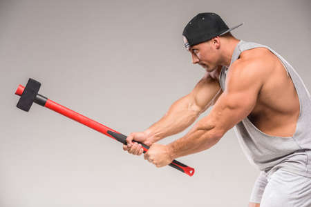 sudio: Muscular bodybuilder with hammer on gray background. Sudio shot.