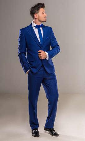 traje formal: Hombre ingenioso hermoso en traje azul y corbata con estilo posando en el estudio. Longitud total. Foto de archivo