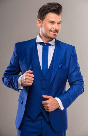 traje formal: Hombre ingenioso hermoso en traje azul y corbata con estilo posando en el estudio.
