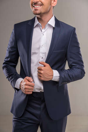 nifty: Handsome nifty man in blue suit on gray background. Stock Photo