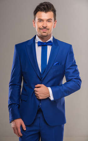 nifty: Handsome nifty man in stylish blue suit and tie posing at studio. Stock Photo