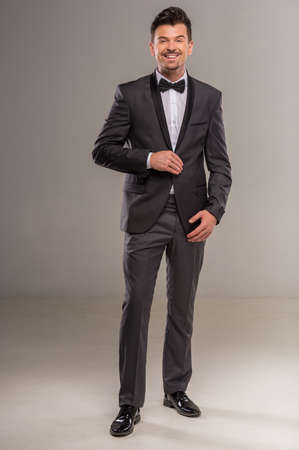Full length image of a young man in dark suit on gray background. Studio shot. Banco de Imagens