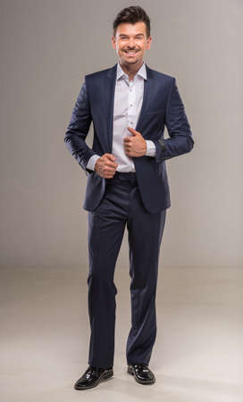 nifty: Full length image of handsome nifty man in blue suit on gray background. Stock Photo