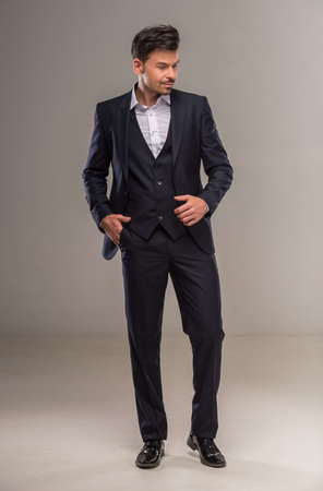 nifty: Handsome nifty man in dark blue suit posing at studio. Full length. Stock Photo