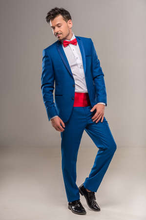 nifty: Full length image of a handsome nifty man in bright cyan suit and red bow-tie. Stockfoto