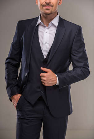 nifty: Portrait of nifty man in dark blue suit on gray background. Studio shot. Stock Photo