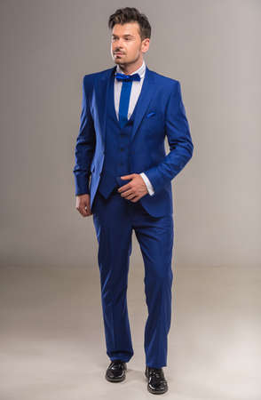 nifty: Handsome nifty man in stylish blue suit and tie posing at studio. Full length.