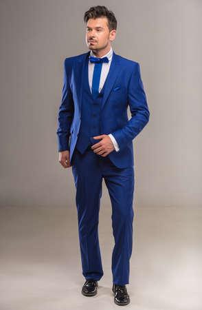 nifty: Knappe handige man in een stijlvolle blauwe pak en stropdas stellen bij studio. Volle lengte.