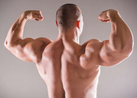 builders: Beautiful muscular man bodybuilder posing back over dark background. Stock Photo