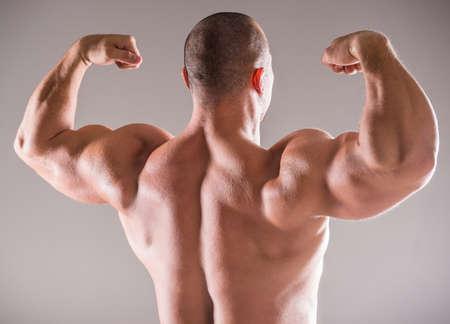 cuerpo hombre: Hermosa culturista hombre musculoso que presentan de nuevo sobre el fondo oscuro.