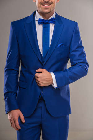 nifty: Handsome nifty man in stylish blue suit and tie posing at studio. Close-up.