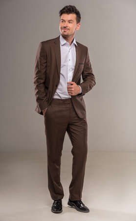 introspective: Full length image of man in stylish brown suit standing on gray background.