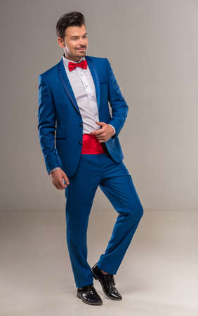 nifty: Full length image of a handsome nifty man in bright cyan suit and red bow-tie. Stock Photo