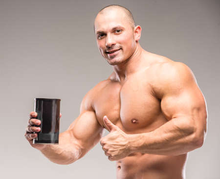 hombre deportista: fisicoculturista muscular que bebe de proteínas en un fondo oscuro. Foto de archivo