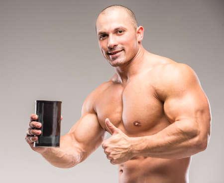 macho man: Muscular bodybuilder drinking protein on a dark background.