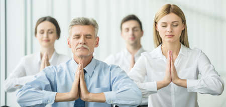 Businesspeople meditating in office, hands put together, concentrating.