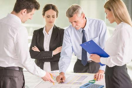 Vier Architekten stehen und Planung an einem Tisch im Büro. Lizenzfreie Bilder