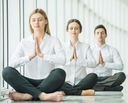 closed business: Business team doing yoga exercise in office together, sitting on the floor with closed eyes. Stock Photo