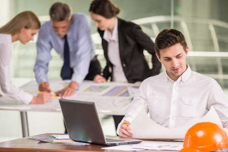 architector: Male architector working on project at workplace, colleagues on background. Stock Photo