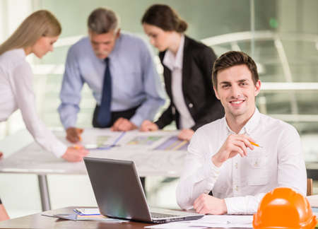 architector: Male architector working on project with laptop at workplace, colleagues on background. Stock Photo