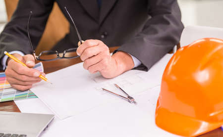 construction project: Close-up of male architect working on blueprints at the office.