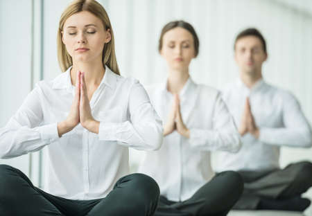 sitting meditation: Business team doing yoga exercise in office together, sitting on the floor with closed eyes. Stock Photo