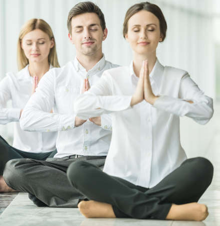 yoga white: Businesspeople meditating in office, hands put together, concentrating.