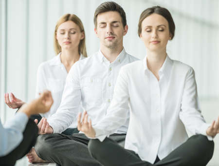 empleados trabajando: La gente de negocios cansadas que se sientan en el yoga plantean en la oficina.