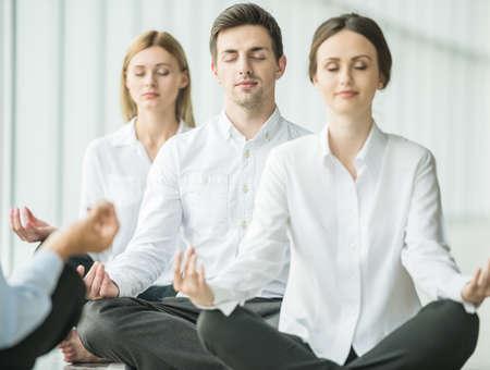 Vermoeide mensen uit het bedrijfsleven zitten in yoga stelt op kantoor.
