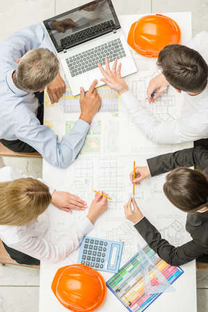 design office: Team of architects working on construction plans at design office.