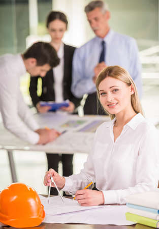 architector: Young female architector working on blueprint at design office, colleagues on background. Stock Photo