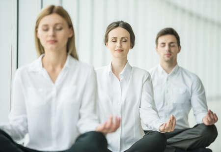 workplace wellness: Coworkers meditating at office, taking break with their eyes closed.