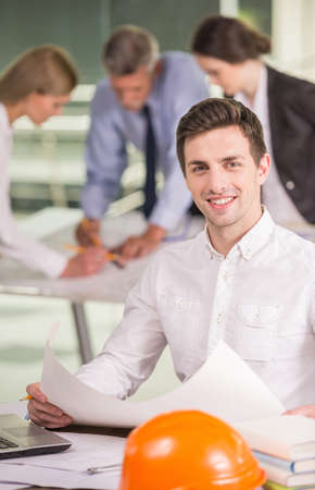 architector: Male architector holding blueprint and smiling to camera, colleagues on background. Stock Photo