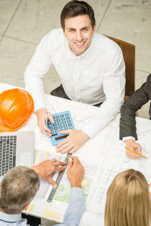 construction project: Meeting the team of engineers working on construction project at the table. Stock Photo