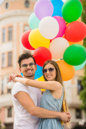 helium: Young couple dressed casual bonding each other and holding bright helium balloons. Stock Photo