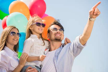 fiesta familiar: Familia feliz con los globos mirando al aire libre en un d�a de verano.