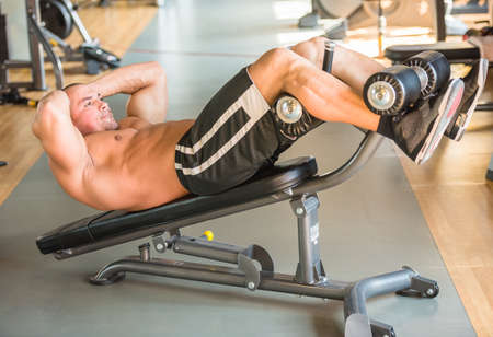laying abs exercise: Sport, lifestyle and people concept - young man making abdominal exercises in gym.