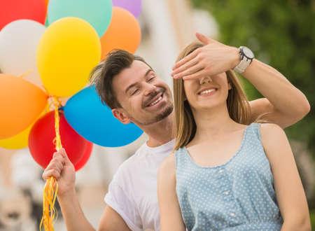 globos de cumpleaños: Hombre hermoso sorprendiendo a su novia con globos de colores. Fecha romántica al aire libre. Foto de archivo