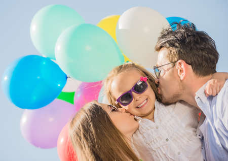 attractive: Young attractive parents with balloons kissing their little daughter on the cheek.
