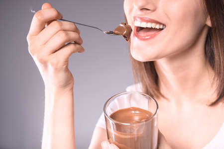 gluttonous: Happy  young woman tasting delicious chocolate paste over gray background. Close-up.