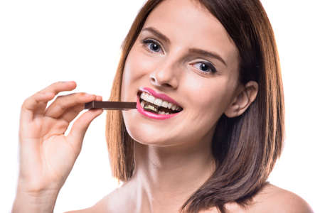 sweettooth: Sweet-tooth. Shirtless woman enjoying chocolate and looking at camera. Studio shot. Stock Photo